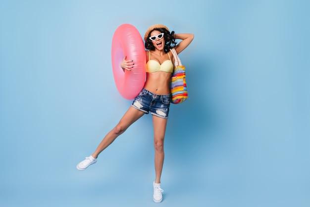 Femme positive sautant avec cercle de natation