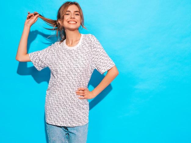 Femme positive souriant. modèle drôle posant près du mur bleu en studio, elle touche ses cheveux
