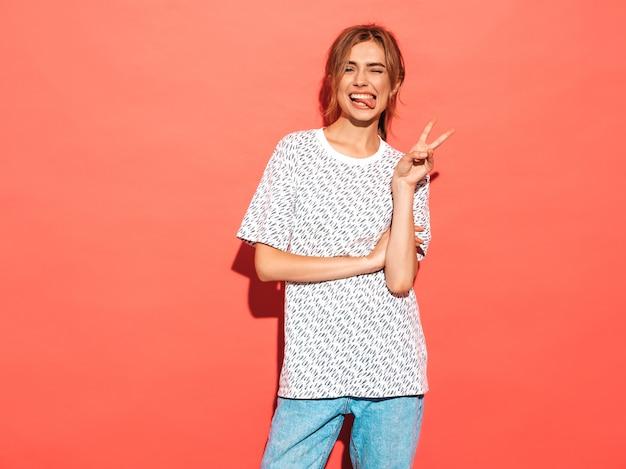 Femme positive souriant. modèle drôle posant près d'un mur rose en studio.