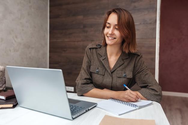 Une femme positive et souriante écrit dans un cahier. fille travaillant à la maison à l'aide d'un ordinateur portable