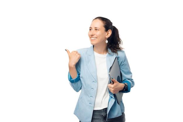 Une femme positive, tenant un ordinateur portable fermé, pointe avec son pouce de côté.