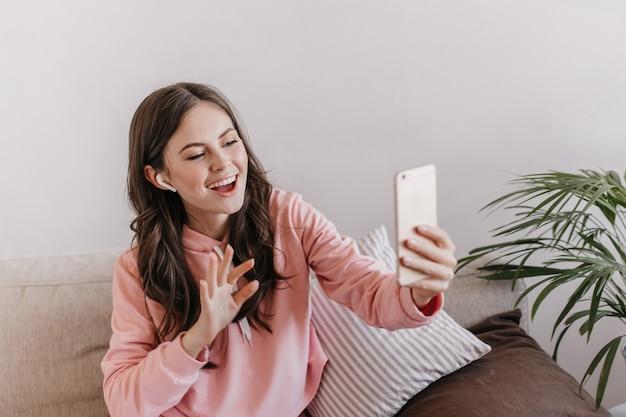 Femme positive en tenue de sport rose, parler au téléphone dans des écouteurs sans fil et assis sur le canapé