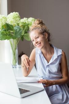 Femme positive travaillant avec des documents sur sill