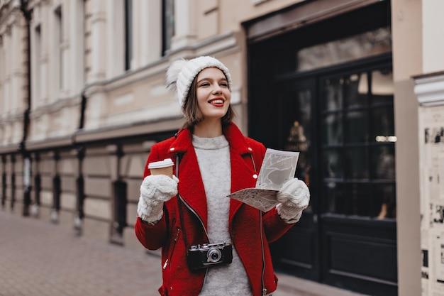 Femme positive en veste chaude rouge, pull en cachemire et chapeau blanc avec des gants se promène dans la ville avec du café. touriste avec appareil photo rétro autour du cou tient la carte.