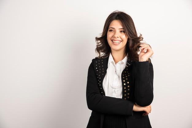 Femme positive en veste noire posant sur blanc