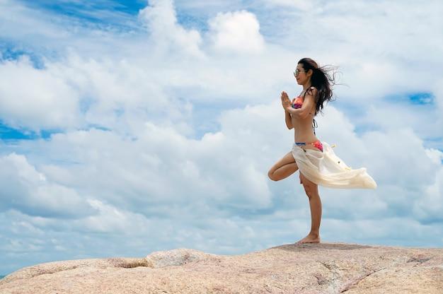 La femme avec une posture de yoga sur la plage