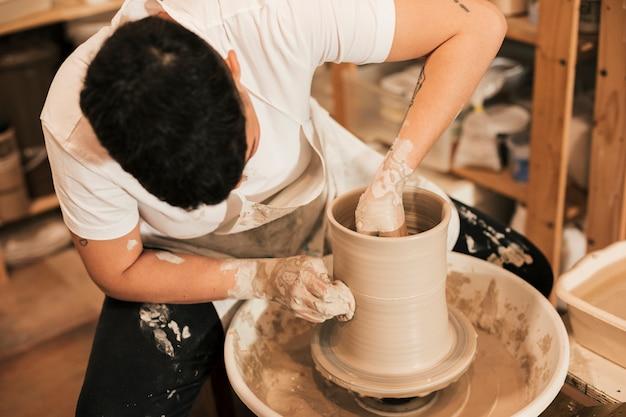 Femme potier accrochant le pot sur le tour de potier dans l'atelier