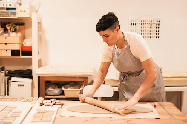 Femme potier aplatissant l'argile avec un rouleau à pâtisserie sur une table en bois