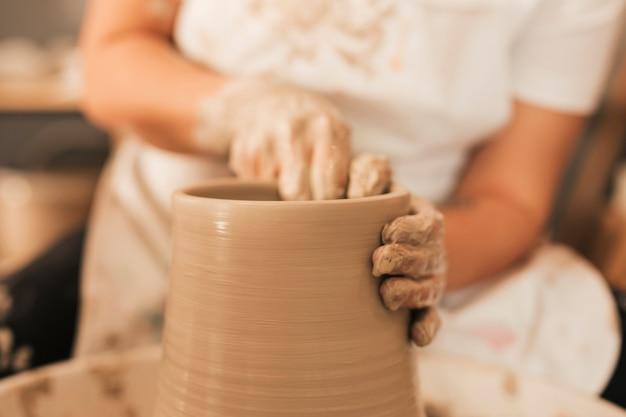 Femme potier travaillant sur le tour de potier