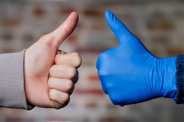 Une femme pouce en l'air dans un gant médical jetable