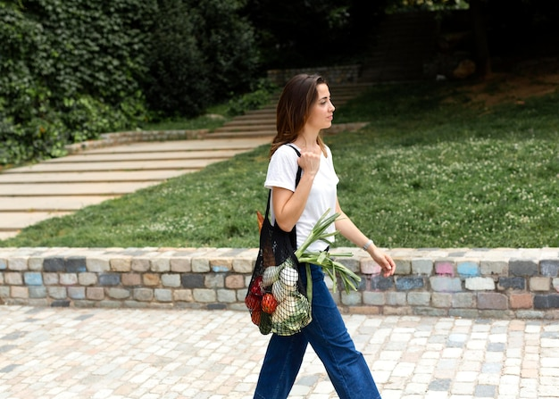 Une femme poursuit un sac d'épicerie durable
