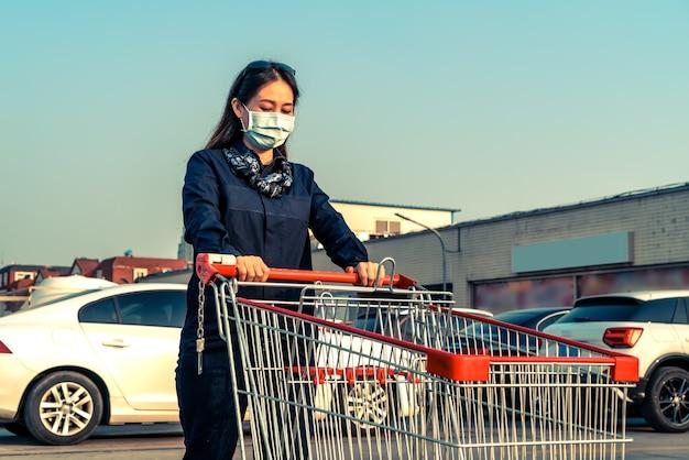 Femme poussant le panier dans le parking