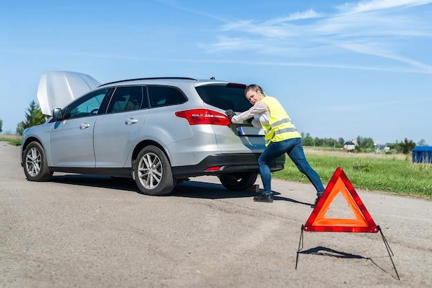 Femme poussant sa voiture cassée sur le bord de la route