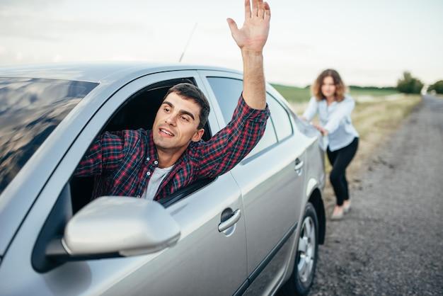 Femme poussant une voiture cassée, conducteur de l'homme