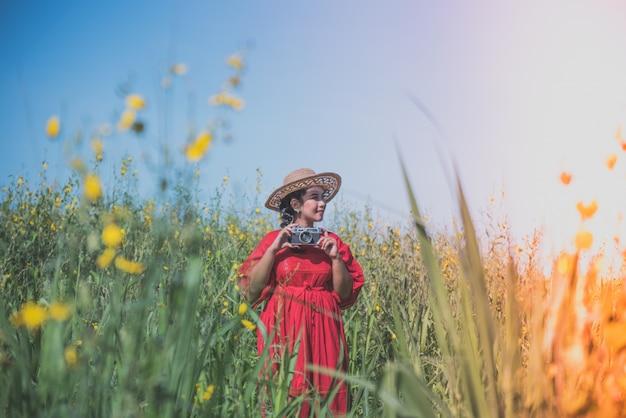 Femme sur une prairie avec un appareil photo