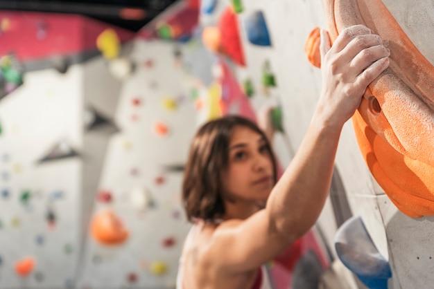Femme pratiquant l'escalade sur mur artificiel à l'intérieur. mode de vie actif et concept de bloc.