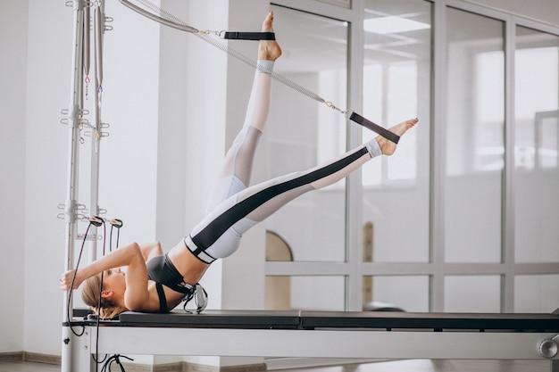 Femme pratiquant le pilates dans un reformeur de pilates