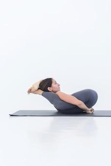 Femme pratiquant le yoga allongée sur le dos pose les jambes derrière la tête sur un tapis sur fond blanc. harmonie et relaxation yogi