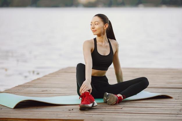 Femme pratiquant le yoga avancé au bord de l'eau
