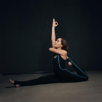 Femme pratiquant le yoga contre un mur sombre texturé