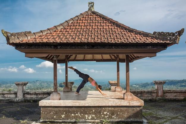 Femme pratiquant le yoga dans le belvédère balinesse traditionnel.
