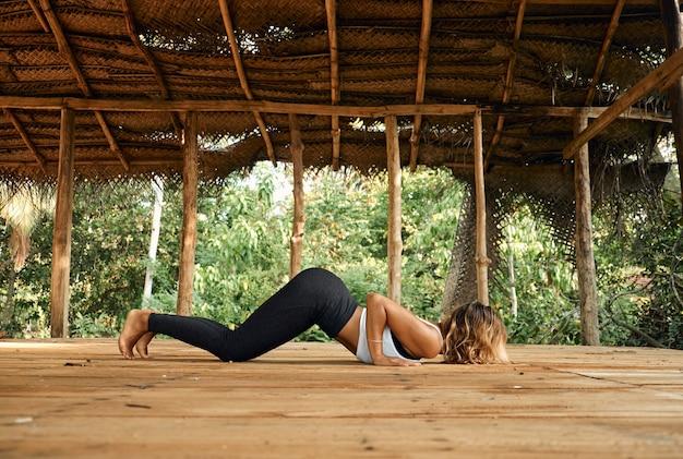 Femme pratiquant le yoga dans le lieu de studio de yoga ouvert tropical