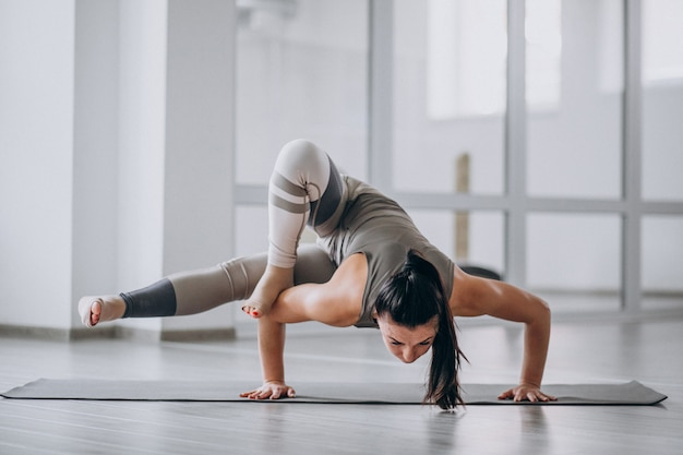 Femme pratiquant le yoga dans la salle de sport sur un tapis