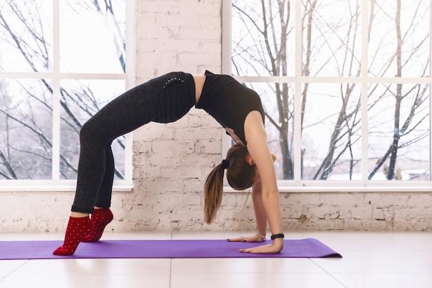 Femme pratiquant le yoga faisant ardha chakrasana pose à l'intérieur de la salle lumineuse sur un tapis de yoga. réchauffer,