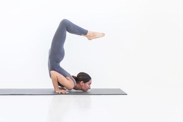 Femme pratiquant le yoga qui s'étend sur fond blanc sur tapis. concept de sport de style de vie