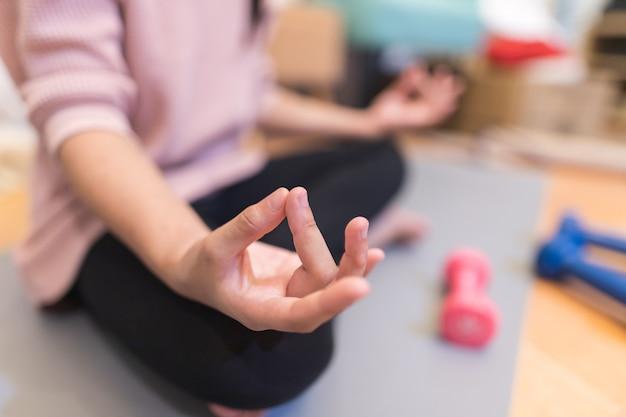 Femme pratiquant le yoga sur un tapis à l'intérieur
