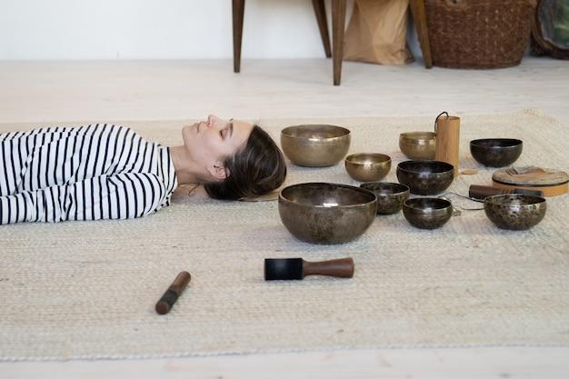 Femme pratique la méditation avec la thérapie des bols chantants tibétains femme méditant à partir d'un massage sonore