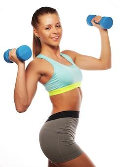 Femme pratique avec des poids de la main