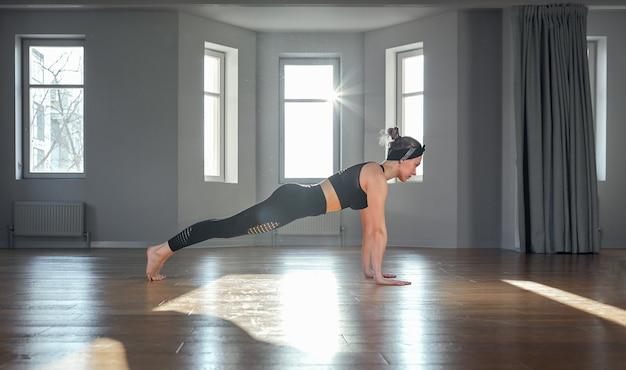 Une femme pratique le yoga dans une salle de fitness à l'aube