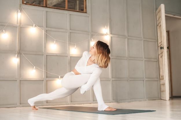 La femme pratique le yoga dans un studio lumineux. asanas femme et yoga.