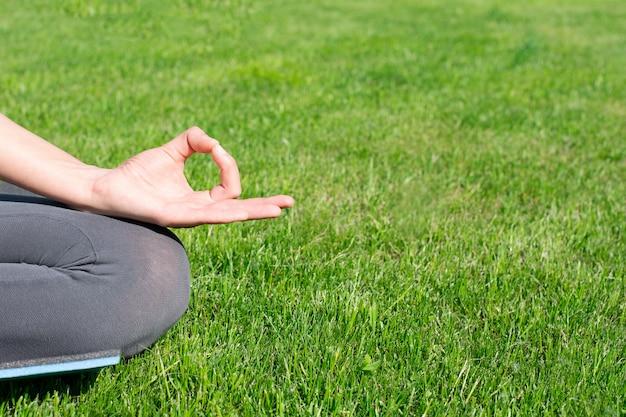 Une femme pratique le yoga à l'extérieur sur l'herbe. espace copie