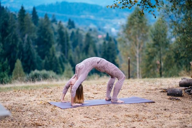 Une femme pratique le yoga le matin dans un parc au grand air.