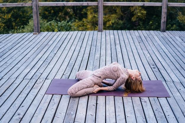 Une femme pratique le yoga le matin sur une terrasse au grand air.