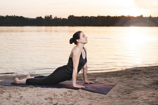 Une femme pratique le yoga sur la rive du fleuve à la plage au coucher du soleil.