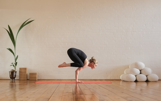 Femme, pratiquer, corbeau, pose, yoga, chez soi