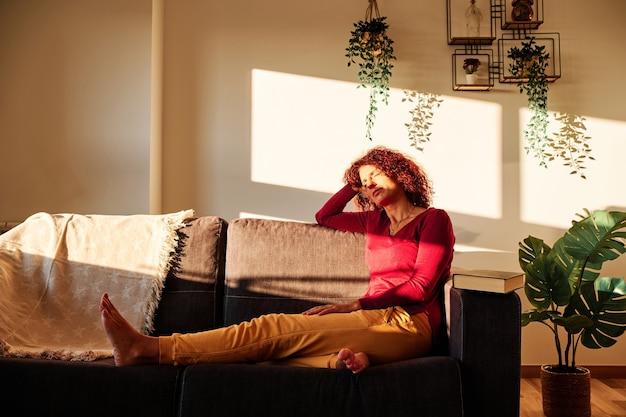 Une femme prenant un bain de soleil sur un canapé à la maison pendant la quarantaine pour une pandémie de coronavirus