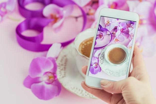 Femme prenant belle photo de tasse de café avec des orchidées roses et des rubans violets sur table avec son smartphone