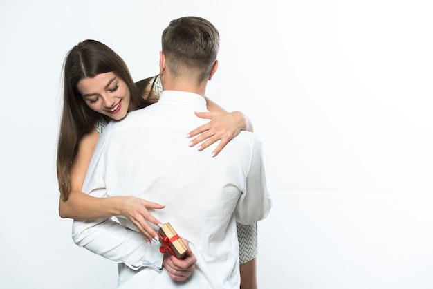 Femme prenant cadeau derrière homme dos