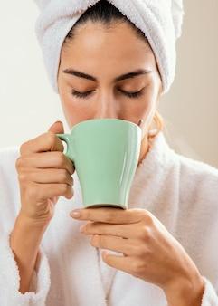 Femme prenant un café à la maison après le bain