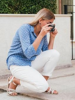 Femme prenant une caméra en plein air