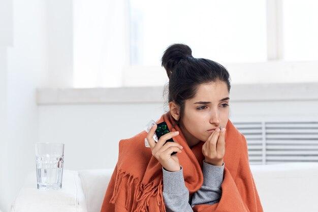 Femme prenant la couverture avec le mécontentement de traitement de médicament à la maison de plaid
