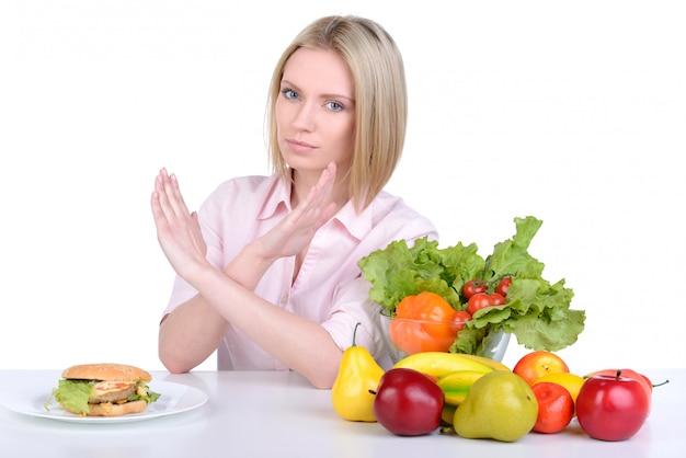 Femme prenant une décision entre une nourriture saine et une restauration rapide.