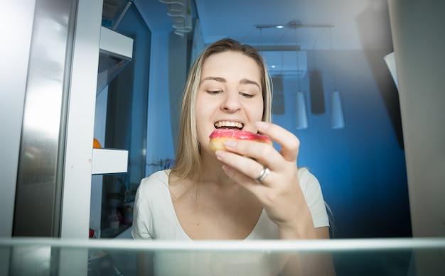 Femme prenant donut de l'étagère du réfrigérateur en fin de soirée