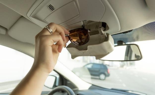 Femme prenant des lunettes de soleil hors du compartiment de voiture spécial