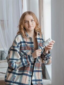 Femme prenant des médicaments. belle fille blonde tenant une bouteille blanche avec des pilules à la main.