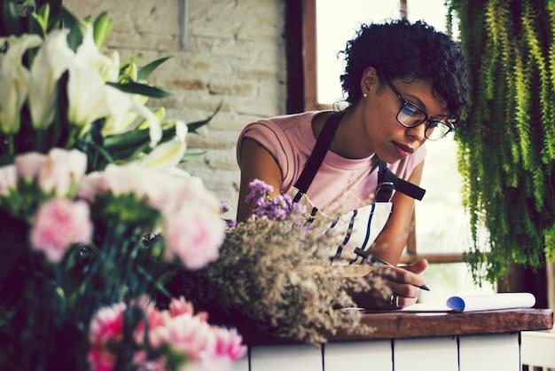 Femme prenant des notes dans un magasin de fleurs